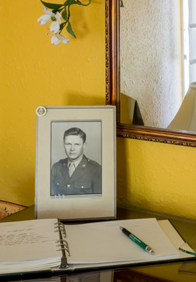Framed picture of man in uniform, gold walls with mirror, guestbook with green pen.