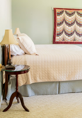Side view of bed with olive bedskirt and cream spread, cream carpet, olive and cream walls, nightstand with lamp.