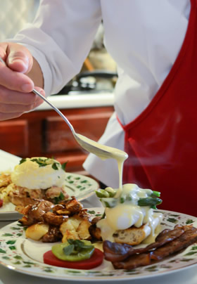 Person with red apron holdingspoon with cheese sauce drizzling over rolled omelet on holly desinged plate.