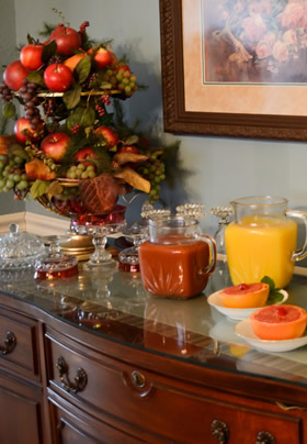 Cherry antique buffet with grapefruit halves with cherries, orange and tomato juice decanters, fruit bown with red apples.