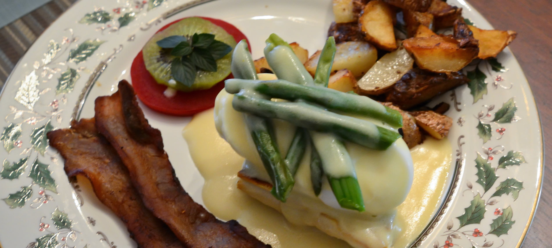 Cream plate with holly design, bacon, fried potatoes, hard-boiled egg with asparagus and cream sauce.
