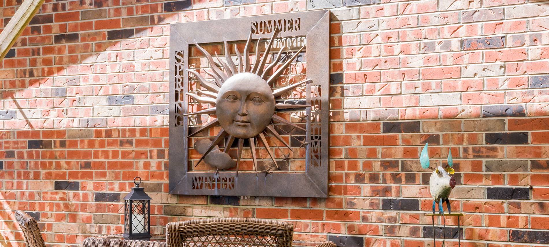 Red brick wall with metal sun hanging listing 4 seasons, wicker chairtops.