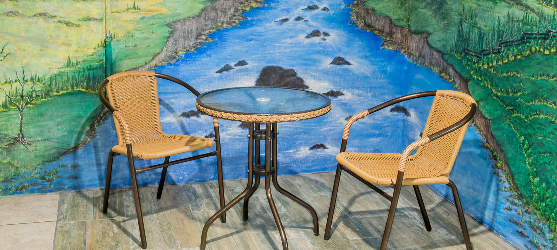 Painting of rocky stream with green grass on sitde, glass table with wicker chairs on wood deck.